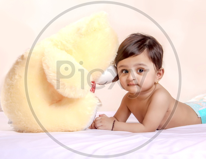 Cute Indian Baby Child Playing With Toys Or Dolls