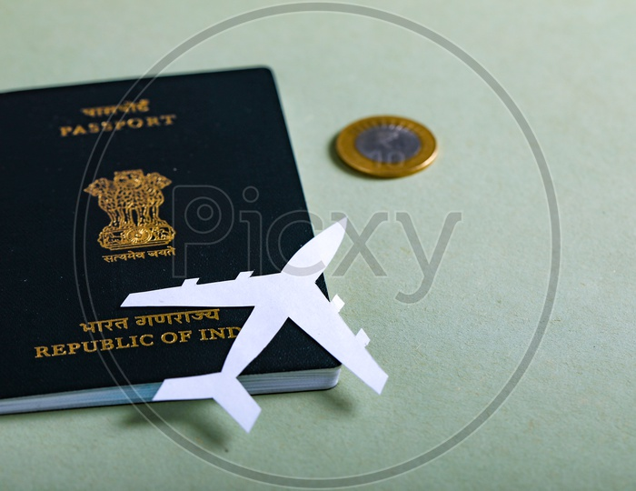 Travel Concept  Indian Passport And Paper Airplane Indian Coin on an Isolated White Background