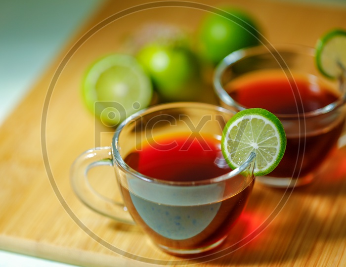 Black Tea In a Glass Cup With Lemons  on an Wooden Table Background