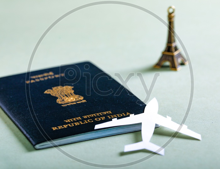 Travel Concept  Indian Passport And Paper Airplane Eiffel Tower Miniature on an Isolated White Background