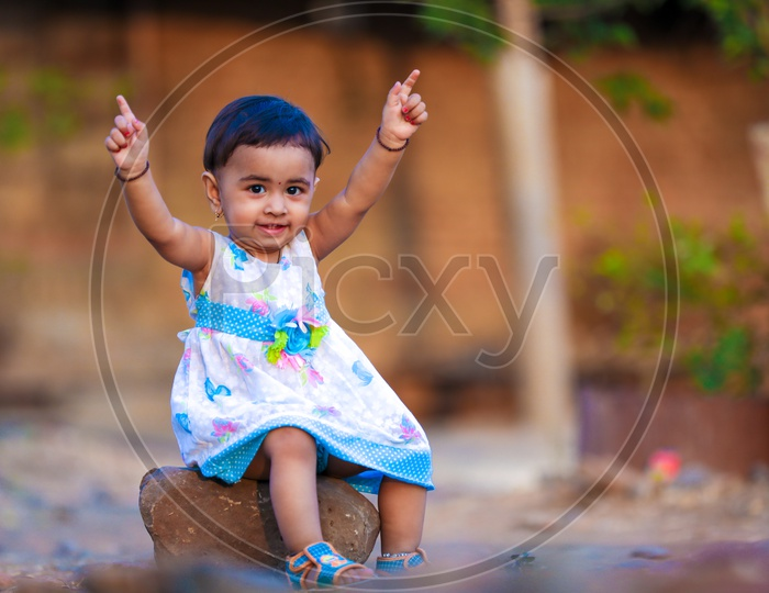 Cute Indian Girl Child or Baby Girl Playing With Multiple Expressions in Outdoor