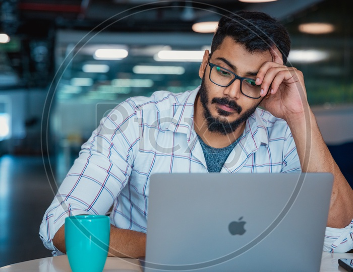 Frustrated Stressed Depressed Thinking Indian  Professional  Young Man Holding Head in Hands Working on Laptop  in Office Work Space