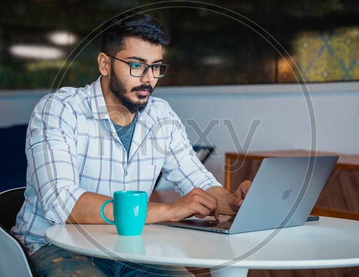 Focused Serious Working Indian Professional Young Man IT Employee  On Laptop In Office Work Space