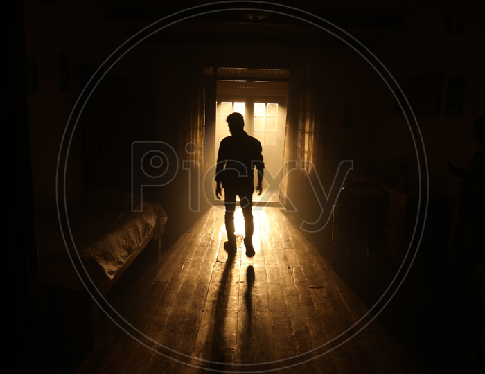 Silhouette Of a Man Standing at  a Door  in a bed room