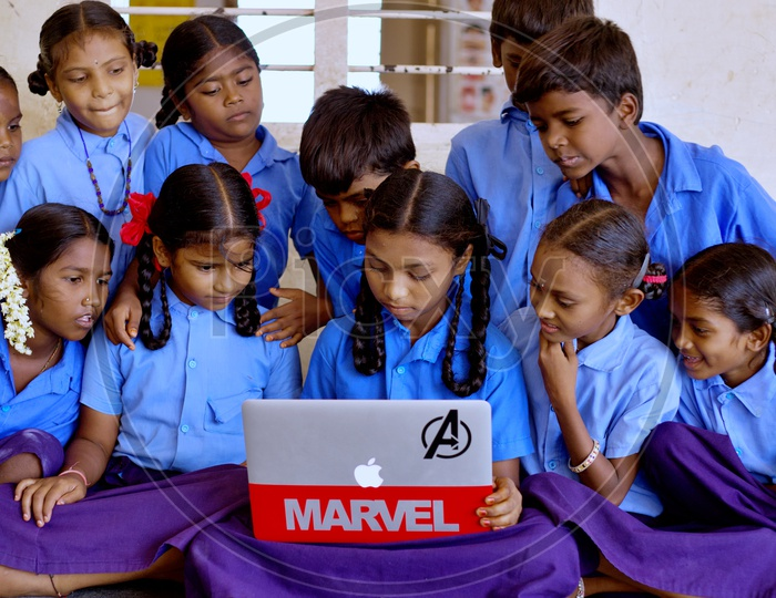 Govt school students watching at a laptop.