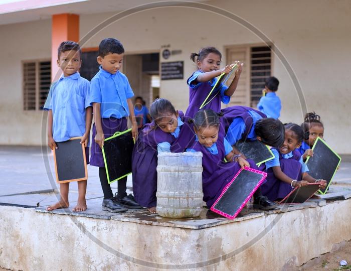 Govt school children washing their slates.