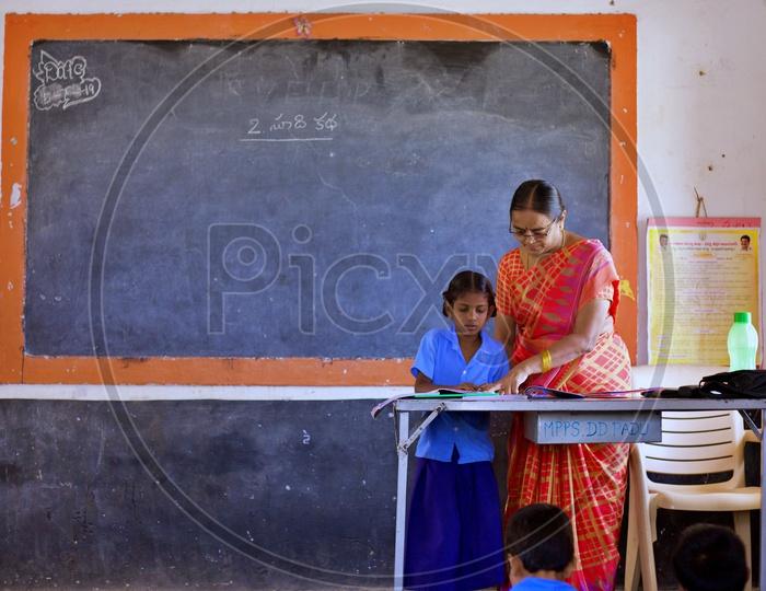 A Govt teacher teaching a girl student how to read.