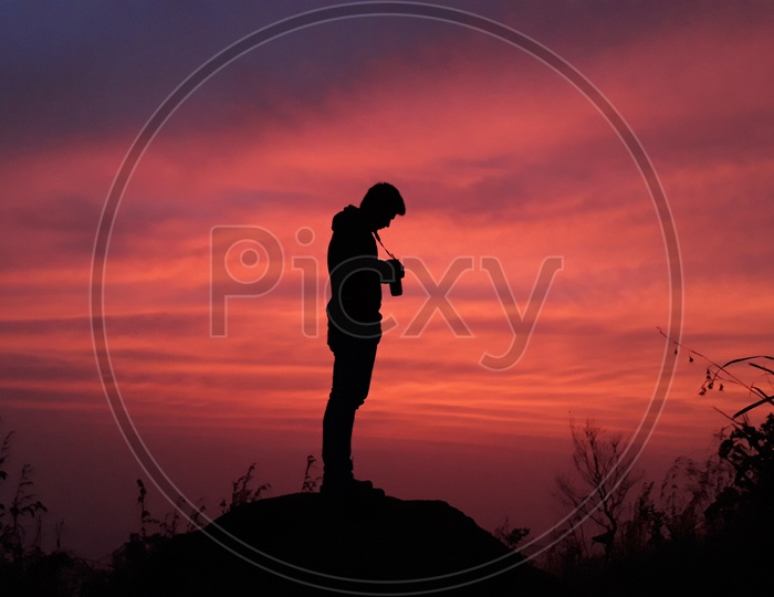 Man with his camera on the top of a hill