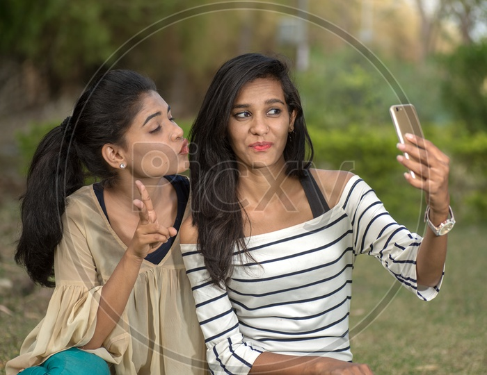 Young Indian Girls students friends  Taking Selfies And Pout in outdoor background