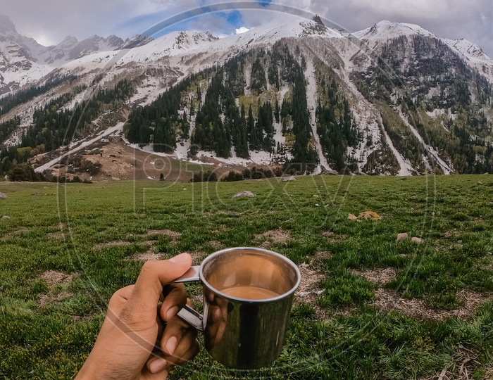 A Trekker Adventurer With a Tea Cup In Hand With a View Of Snow Capped Mountains In  Background