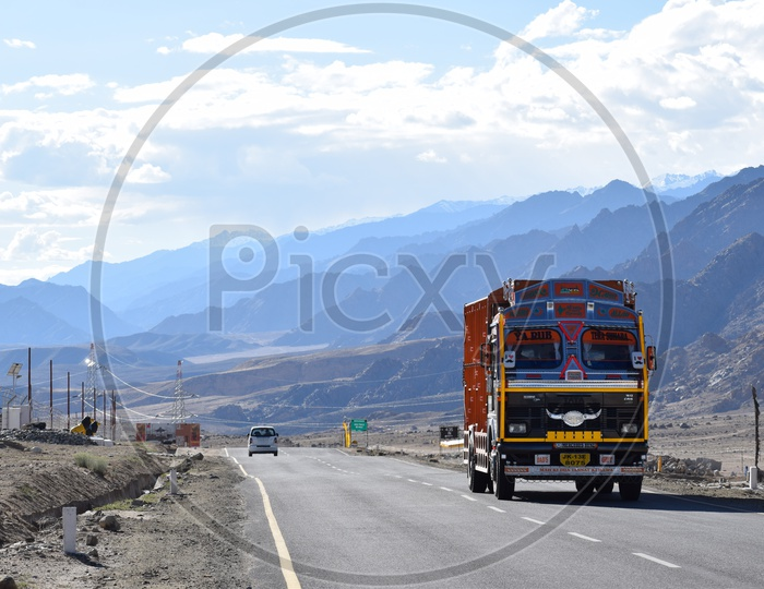 Lorry passing on the highway with the backdrop of Himalayas