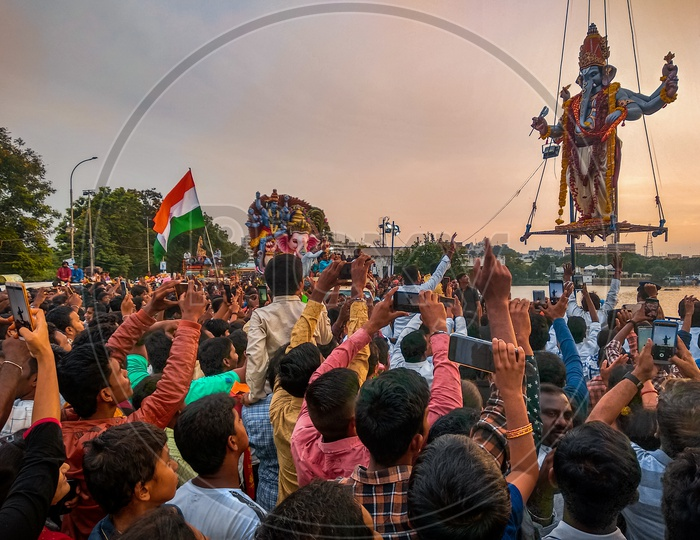 Ganesh immersion, people taking pictures of Ganesha with mobile while nimarjanam