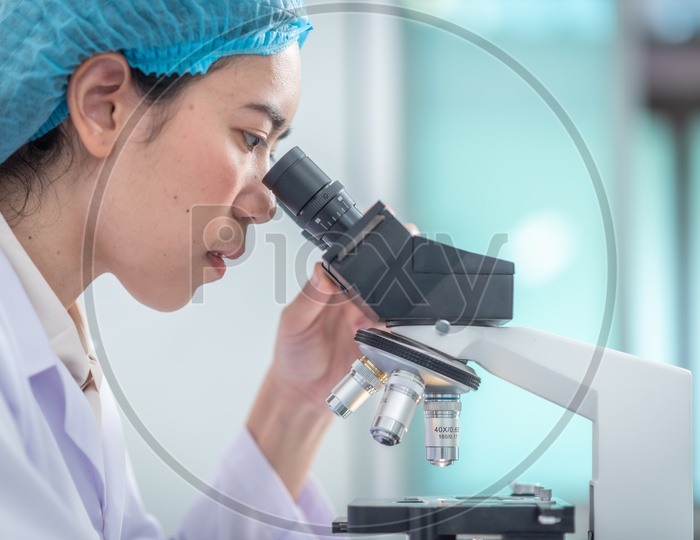 Asian Student Using Microscope in Pharma Laboratory