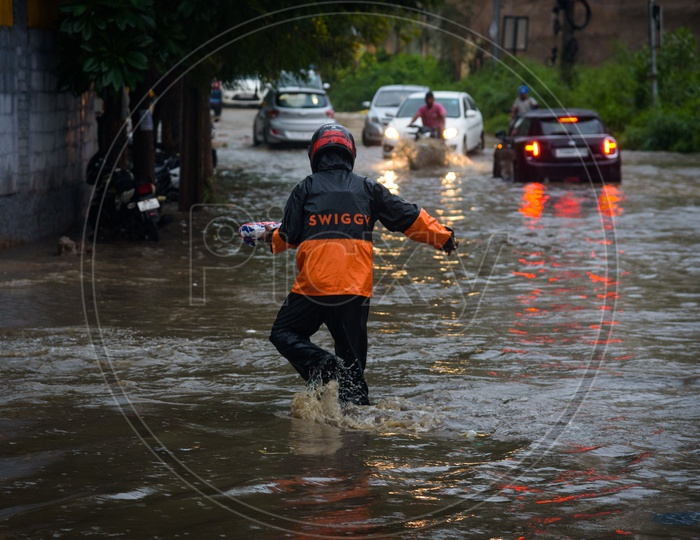 Swiggy Delivery Boy delivering food in rain flooded water on road