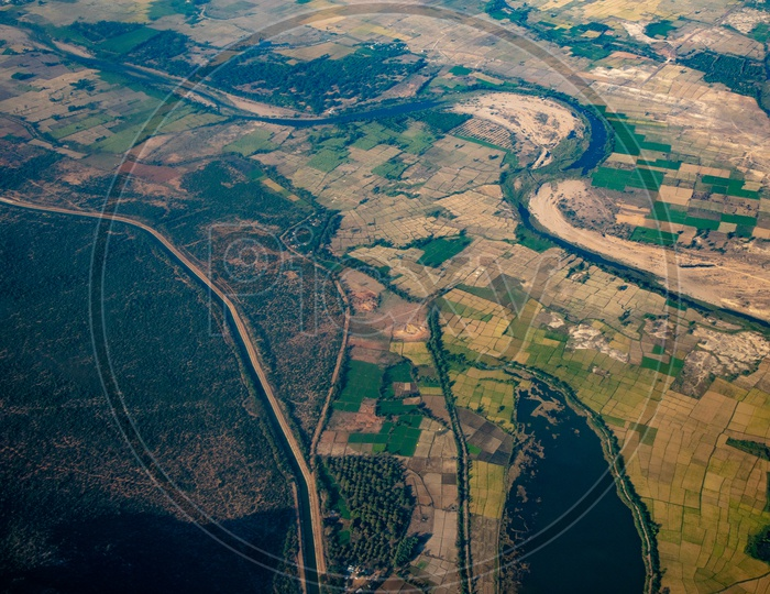 Aerial View Of Green Paddy Fields And  Roads  From Flight Window