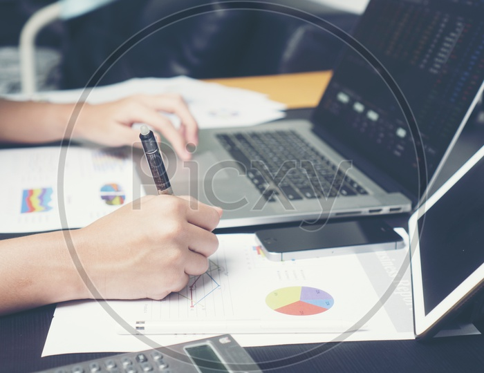 Employee Or Businessman Working On Laptop With Paperwork Of Business Analysis Charts At Office Desk With Hands Closeup