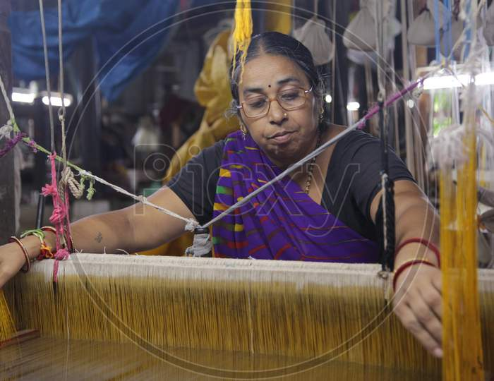Indian Woman coloring the weaving thread