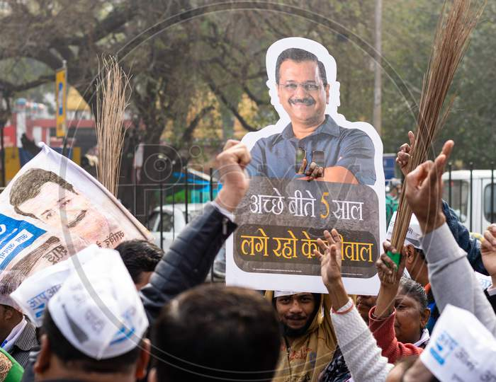 Aam Aadmi Party AAP supporters holding cutout of Arvind Kejriwal and brooms during a rally for Delhi Assembly Election