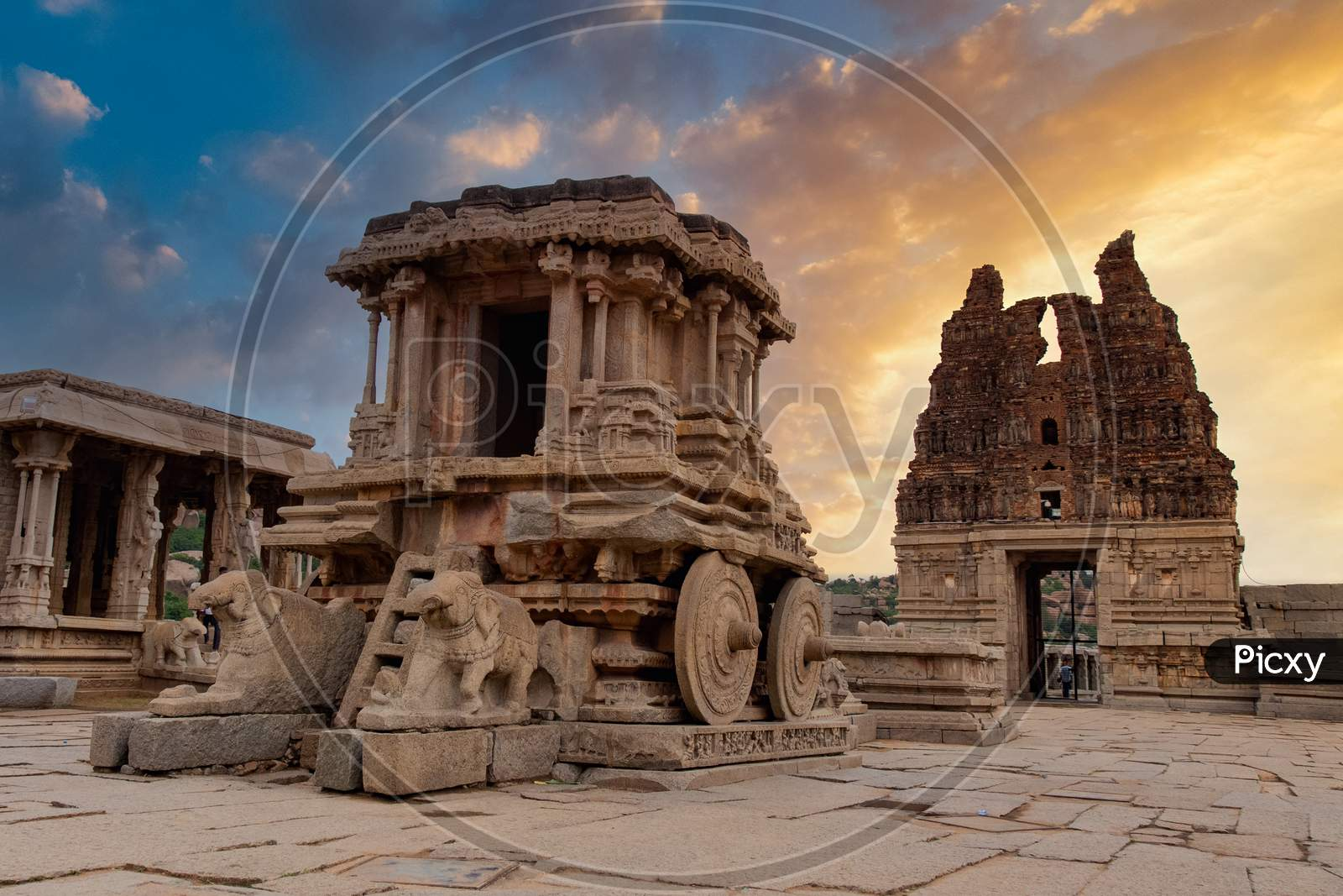 Stone Chariot In Vittala Temple  With Sunset Golden Clouds In Background