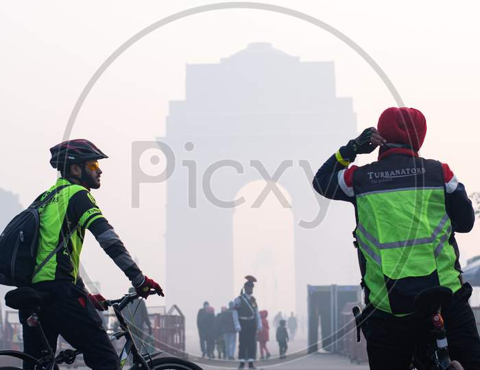 Two cyclists in the foggy morning during winters in front of India Gate in Delhi