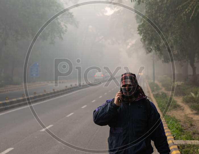 A man covering his face with muffler and wearing winter wears in the foggy morning during winters in Delhi