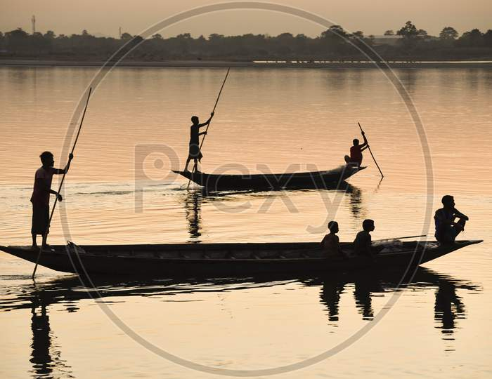 Silhouette Of  Indian Fishermen Fishing In Beki River During Sunset, At Sarbhog In Barpeta District Of Assam