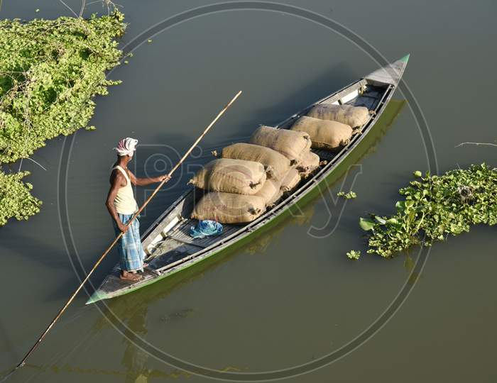 Indian Man Paddle A Boat In A Lake Loaded With Rice Grain Bags, To Sell In The Nearest Market, At Kayakuchi Village In Barpeta District Of Assam