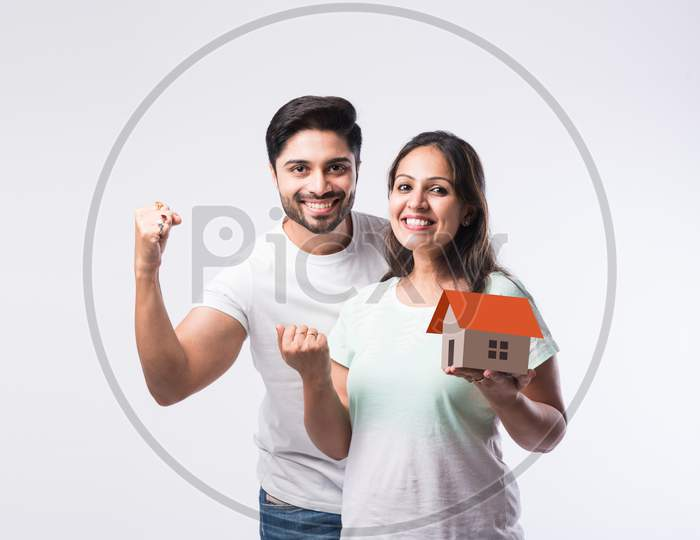 Concept Real Estate Housing And Young Indian Couple Family - Husband Wife Holding 3D Paper Model