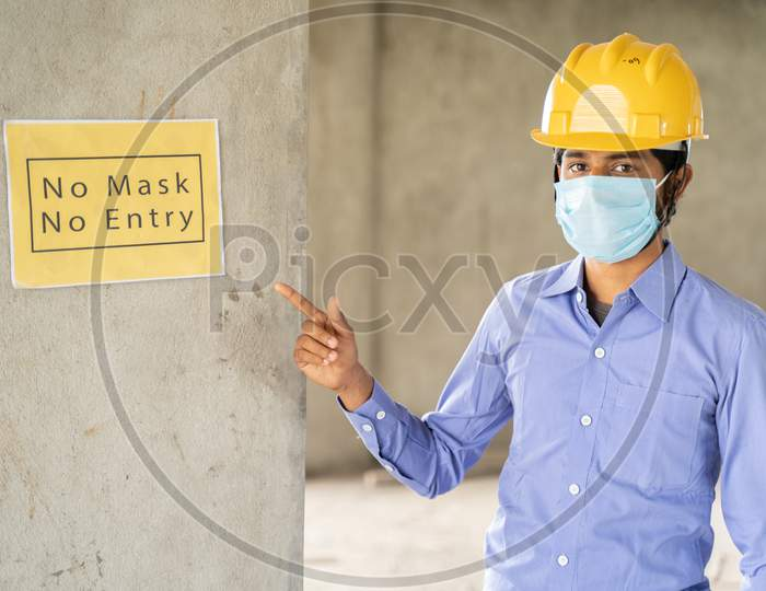 Worker Pointing No Mask No Entry Signage Notice Board On Wall At Working Construction Site To Protect From Coronavirus Or Covid-19 At Workplaces - Concept Of Health And Labor Safety During Pandemic