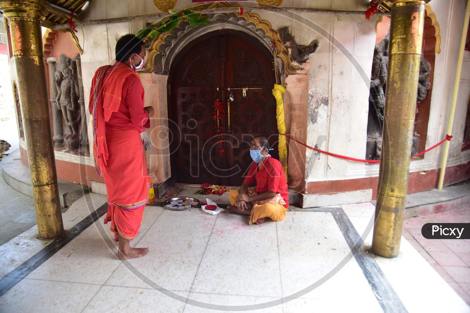A priest sits the inside the premises of Kamakhya Temple, as it re-opens for public after a gap of nearly six months due to coronavirus lockdown with certain restrictions, in Guwahati, on October 11, 2020