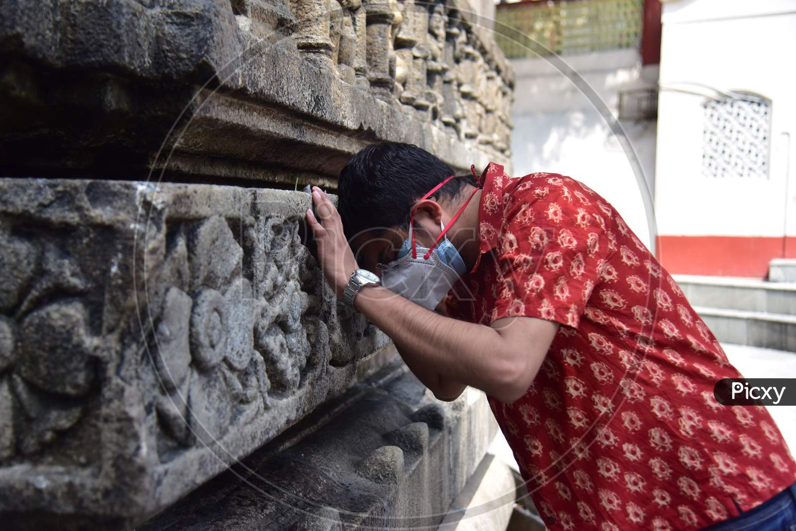 Indian devotees offer prayers by touching the Kamakhya temple after re-opens for public after a gap of nearly six months due to coronavirus lockdown with certain restrictions, in Guwahati, India on October 11, 2020.