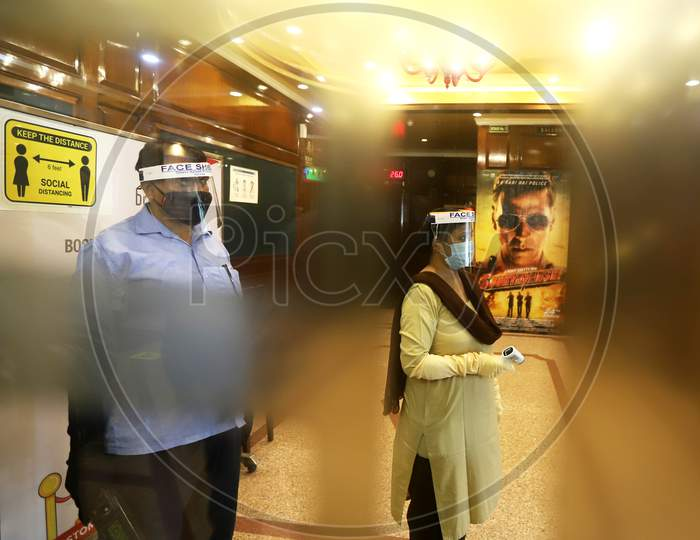 Workers wear facemasks and face shields  inside a theatre during a sanitisation work ahead of the scheduled reopening of cinema theatres on October 15 as the Covid-19 coronavirus imposed lockdown eases further in New Delhi on October 13, 2020.