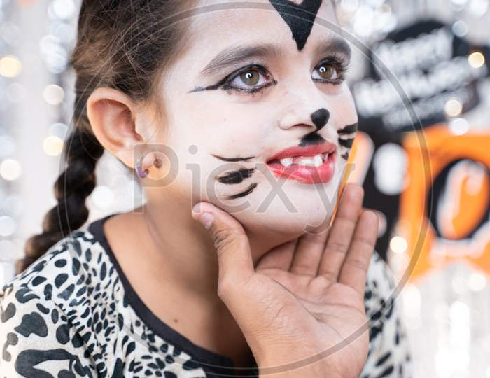 Parent Helping Her Daughter To Get Ready For Halloween By Doing Make-Up - Concept Of Halloween, Holiday And Childhood Festival Celebration And Preparation.