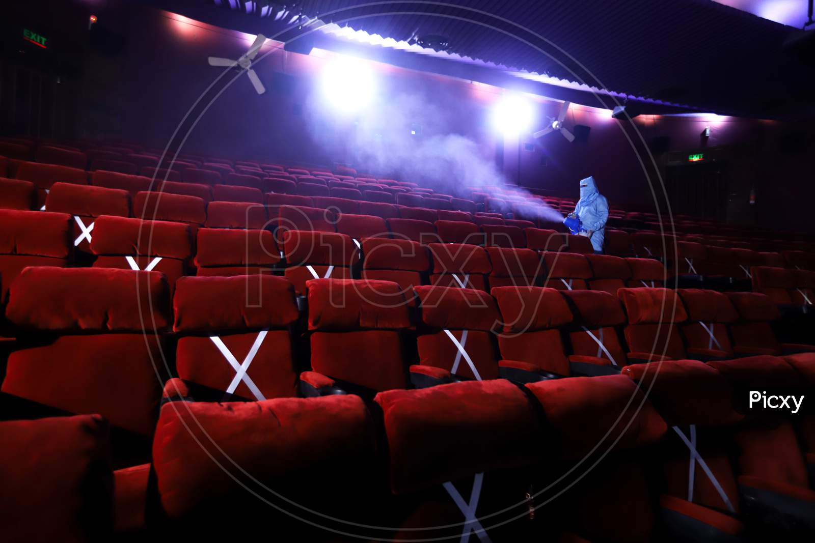 A worker sanitises inside a theatre hall ahead of the scheduled reopening of cinema theatres on October 15 as the Covid-19 coronavirus imposed lockdown eases further in New Delhi on October 13, 2020.