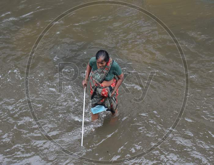 an elderly woman tries to walk with a stick on a flood affected road in Tolichowki, Hyderabad on October 14, 2020.