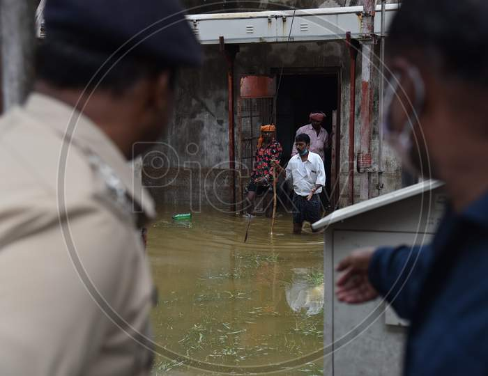 workers come out after being rescued by OCTOPUS team from a factory that got inundated due to the overflowing of Palle Cheruvu on October 14, 2020.