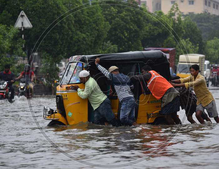 GHMC workers and passers by try to push an auto that got stuck in the rain water in Tolichowki,Hyderabad on October 14, 2020.