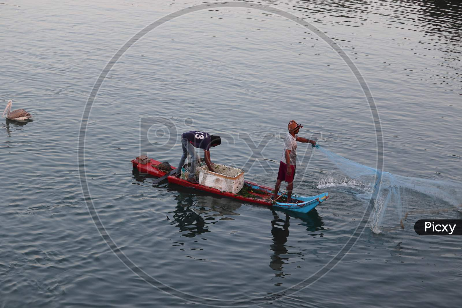 Fisherman Throws Nets Into The Water To Catch Fish From The Boat
