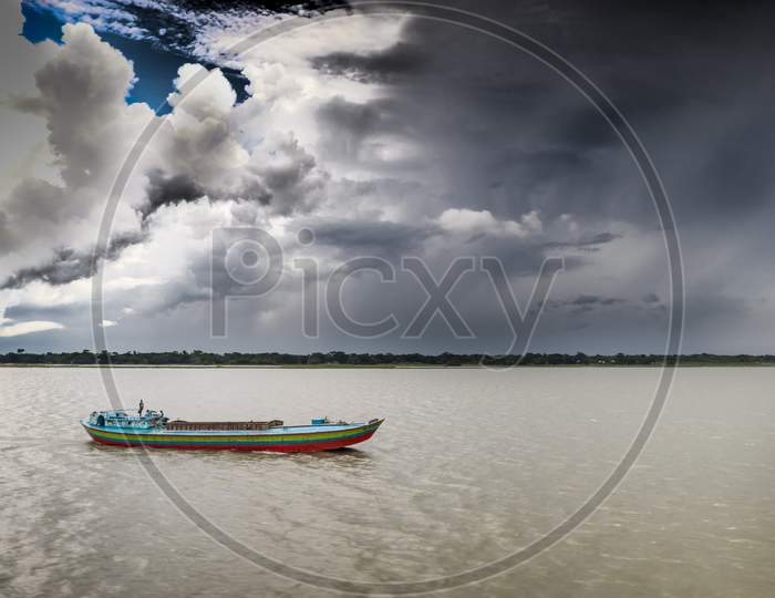 A Boatman Moving To City Under Summer Cloudy Sky