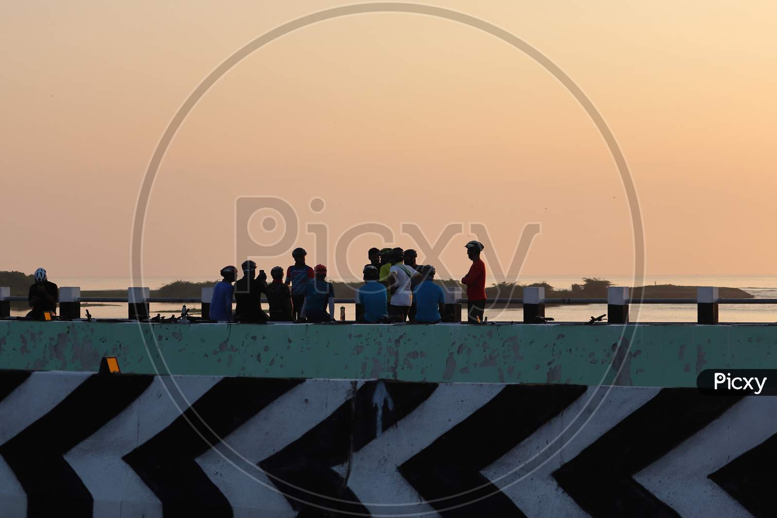 A Group Silhouette Sport Men Gather Atop A Bridge Near The Seaside In The Morning While Doing Selfie Photography
