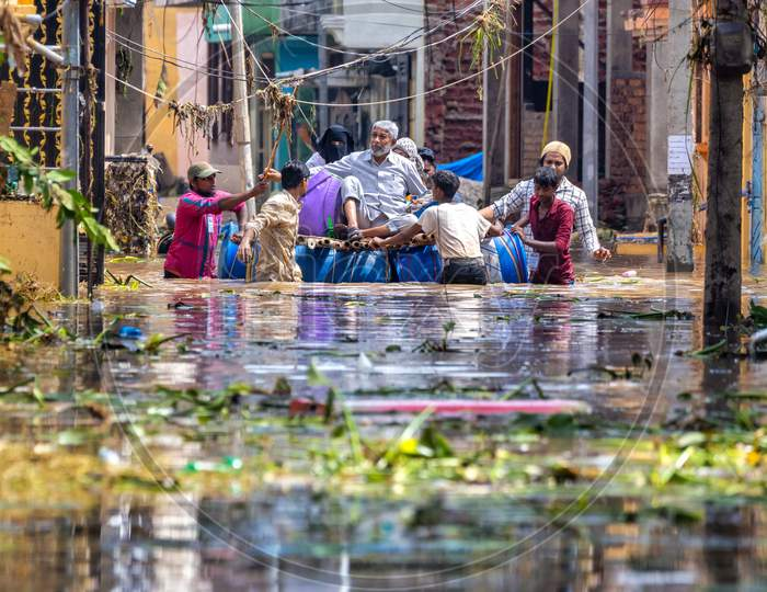 Locals helping the residents to vacate from their houses in the flood water occupied streets in the Hafiz Baba Nagar due to Hyderabad floods