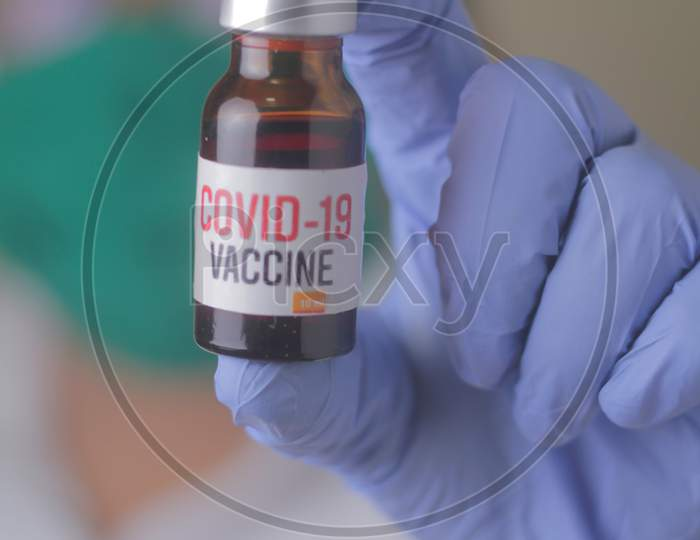 Doctor, Nurse, Scientist, Researcher Hand In Blue Gloves Holding Flu, Measles, Coronavirus, Covid-19 Vaccine Disease Preparing For Human Clinical Trials Vaccination Shot, Medicine And Drug Concept.
