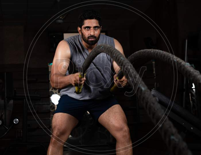 Asian Indian Man Doing Exercise With Battle Rope In Gym