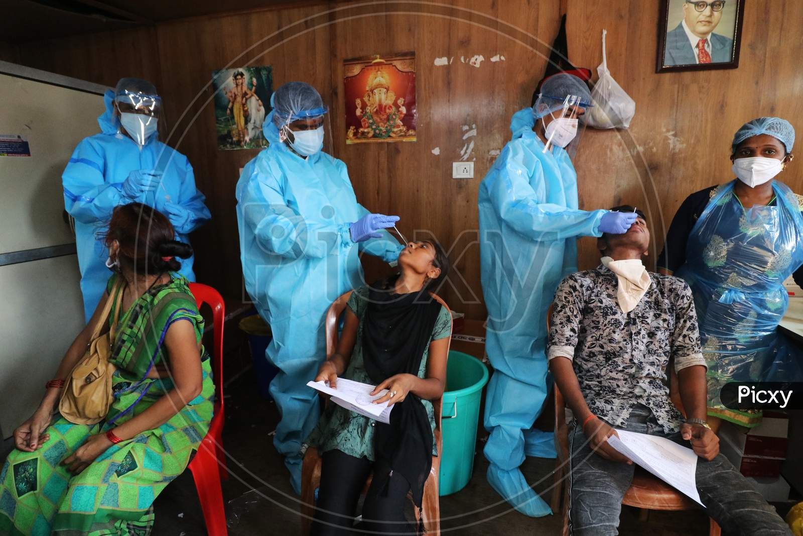Health workers in personal protective equipment (PPE) collect swab samples from migrants who returned from their village at a railway station during a rapid antigen testing campaign for the coronavirus disease (COVID-19), in Mumbai, India, October, 2020.