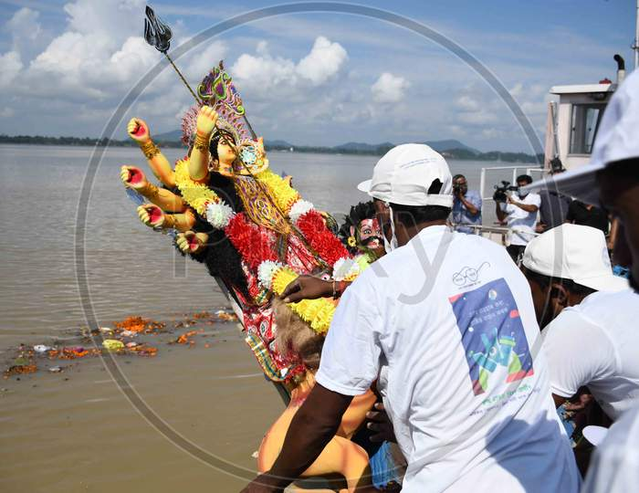 Municipal workers immerse an idol of the Hindu goddess Durga in the waters of the river Brahmaputra on the last day of the Durga Puja festival in Guwahati on Oct 26,2020.