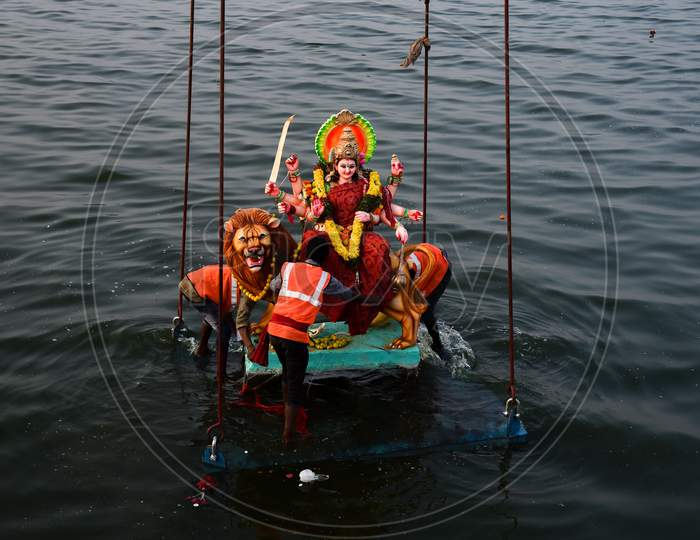 GHMC workers carry the Idols of Goddess Durga for immersion in Hussain Sagar on the last day of Navratri/Vijaya Dashami/Durga Puja in Hyderabad, October 26,2020.