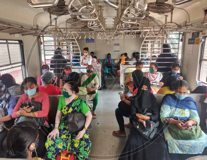 Women wearing protective face masks commute in a suburban train after authorities resumed the train services for women passengers during non-peak hours, amidst the coronavirus disease (COVID-19) outbreak, in Mumbai, India, 2020.