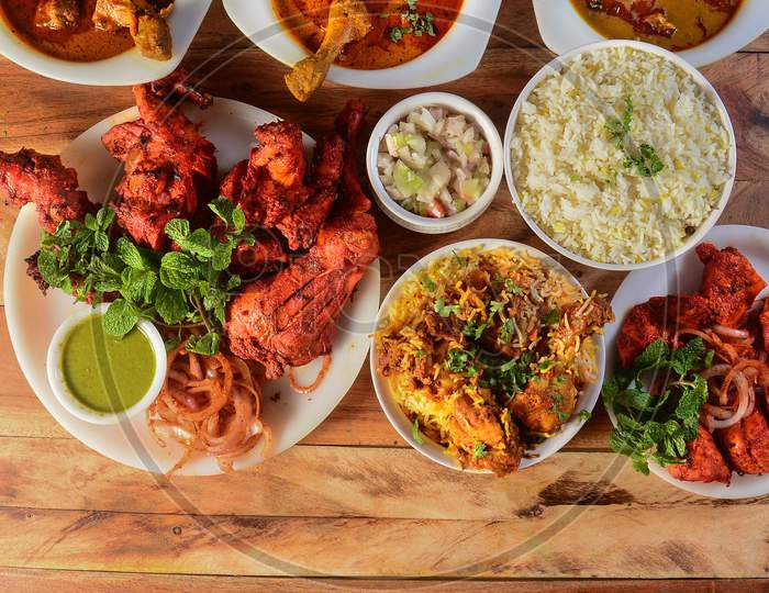 Assorted Indian Foods Tandoori Chicken,Chicken Biryani, Chicken 65 And Chicken Masala On Wooden Background. Dishes And Appetizers Of Indian Cuisine