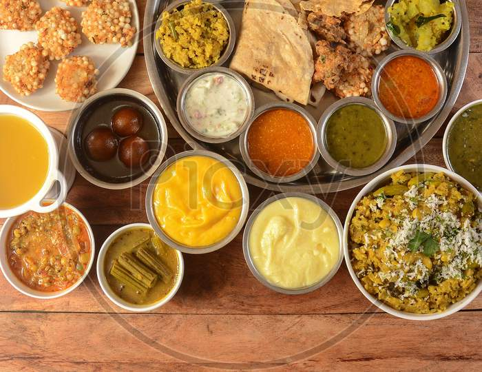 Assorted Indian Food Veg Thali On Wooden Background. Dishes And Appetizers Of Indian Cuisine
