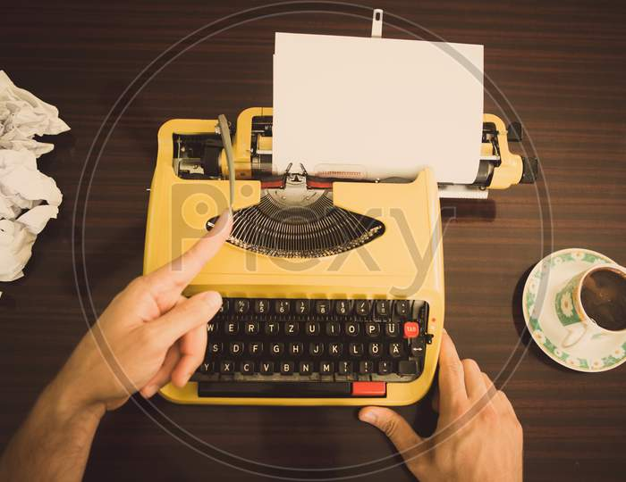 The Writer Is Typing Text On An Old Yellow Typewriter And Starts A New Line Of Text.